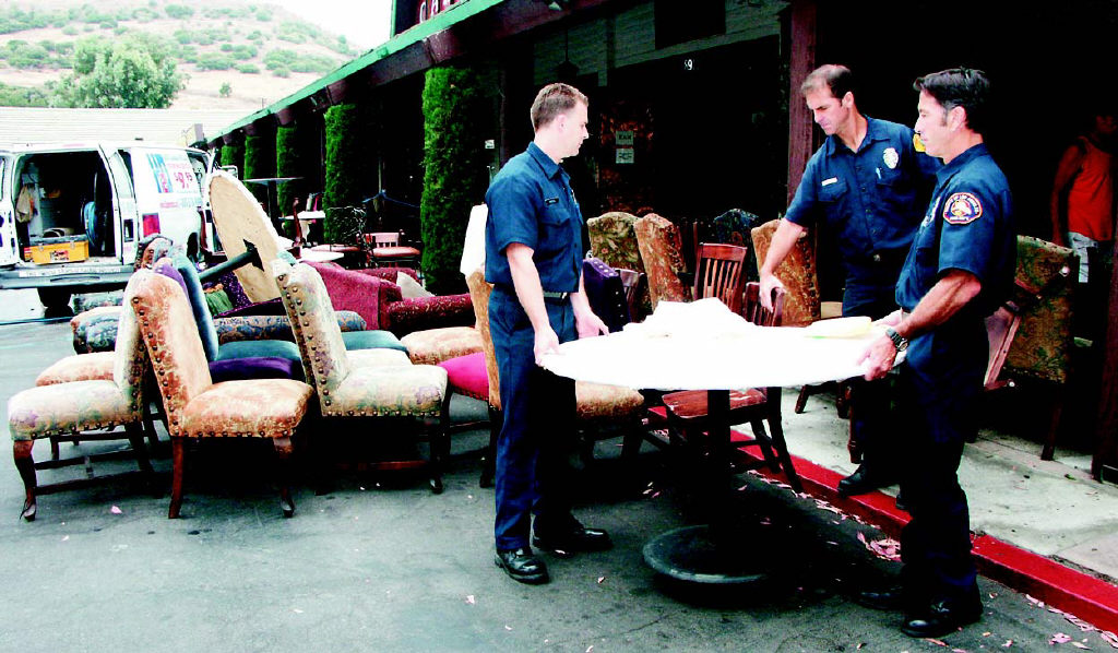 LISA ADAMS/The Acorn  SERVING THE PUBLIC-L.A. County firefighters (left to right) Mike McFaul, Kevin Muno and Chris Avezzie remove furniture to minimize the damages of a flood at The Canyon, a popular nightspot in Whizin's Shopping Center in Agoura Hills. An underground water main burst yesterday morning and flooded the facility. Lance Sterling, owner of The Canyon, vowed that it would reopen today.