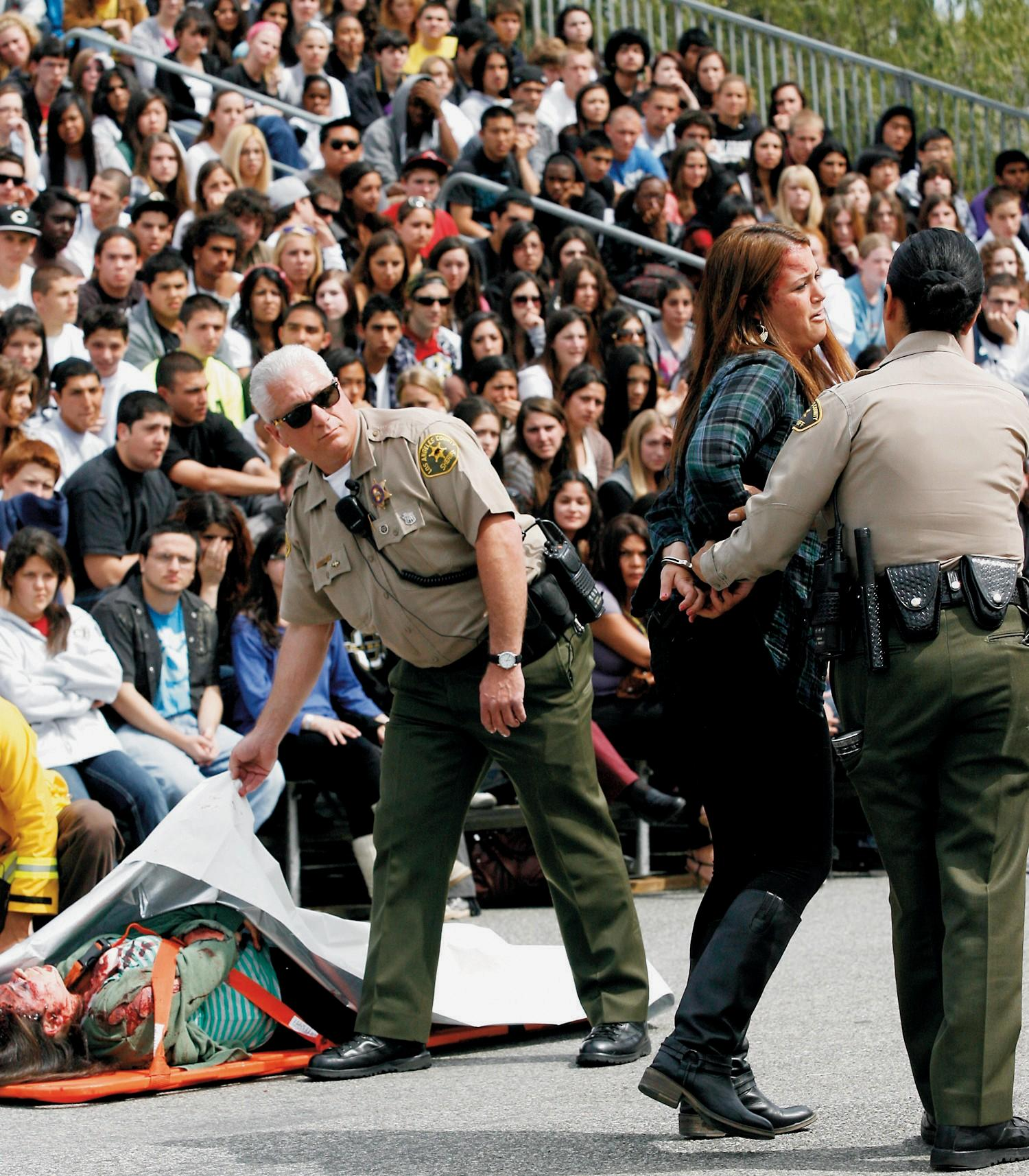 """SCARED STRAIGHT—Above,  Lost  Hills  sheriff's  deputy Robert DeSantis assists in a mock accident scene at Calabasas High School's """"Every 15 Minutes"""" drunk driving awareness program. Below,  firefighters  take  away  crash  """"victim""""  Alex Varonos on a stretcher. Visit www.every15minutes.com."""
