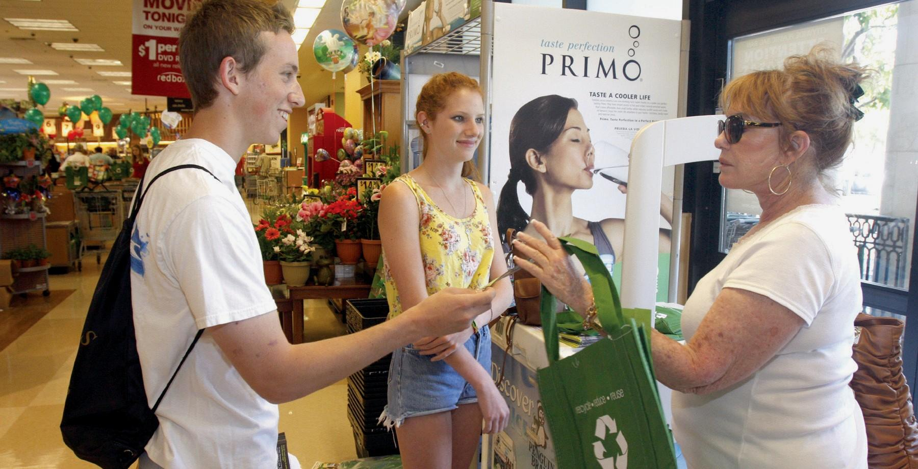BAG IT—Calabasas resident Beth Lin, right, receives two free reusable shopping bags from volunteers Max Aveis, 17, and Hannah Frankl, 15, at Ralphs supermarket in The Commons July 1.