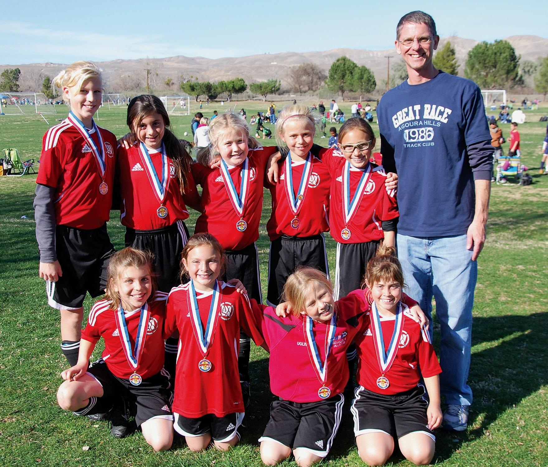TASTE THE VICTORY—The AYSO Regional 4 U10 All- Stars, Honey Badgers, took first place in the Directors Cup Tournament in Bakersfield. Back row, from left: Caitlyn Danovich, Penny Smith, Aubrey Billig, Marley Volk, Malia Cohen and Coach Ted Volk. Front row: Carly Fernandez, Julia Dinerman, Noa Volk and Phoebe Reed.