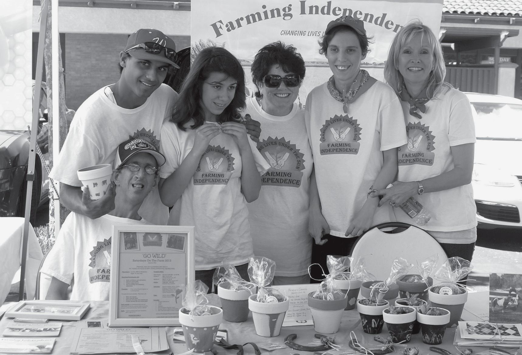 YOUNG ENTREPRENEURS—Special needs adults sell their crafts and baked goods at the Westlake Village farmers market on Sun., July 29, culminating the month-long Saturdays On The Farm program in Old Agoura. Some of the participants are, Ben, seated, standing from left: Michael, Kayley, volunteer Chris Thorkill, Lauren and program founder Sheila Mayfield. A second session of Saturdays On The Farm begins this weekend. For more information, visit www.farmingindependence.org.