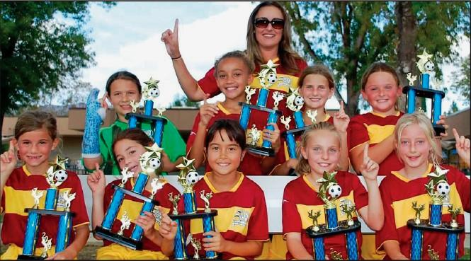 BIG WINNERS—Coach Georgia Mitchell stands behind the Macaws after they win the AYSO Region 4 girls' U-10 championship on Nov. 15. The team members are, seated from left, Leah Gelick, Rebecca Kusnier, Leila Torres, Ava Sylvester and Laney Winders. Standing: Madison Lata, London Gamble, Dakota Chase and Savannah Mitchell.
