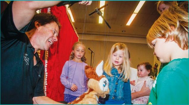 SHOWING RUDOLPH THE ROPES— Vsev Krawczeniuk of the Franklin Haynes Marionettes Company gives 3-year-old London Cooke of Westlake Village a close up look at Rudolph on strings at the Santa's New Sleigh event at the Grant Brimhall Library on Dec. 13.