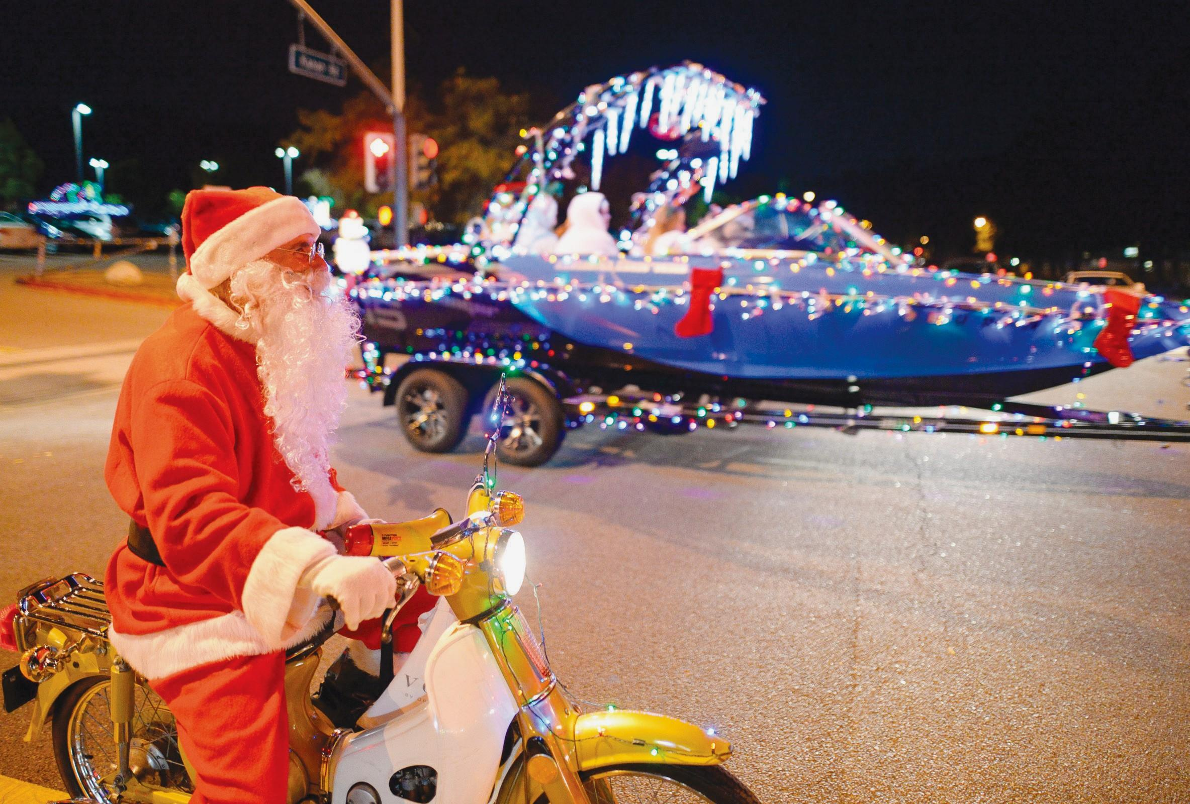 HO, HO, GO SLOW—Santa Claus Jerry Ramer of Oak Park helps direct the 16th annual Oak Park Boat Regatta as it departs Oak Park High School on Dec. 20. The quirky parade has become an annual tradition.