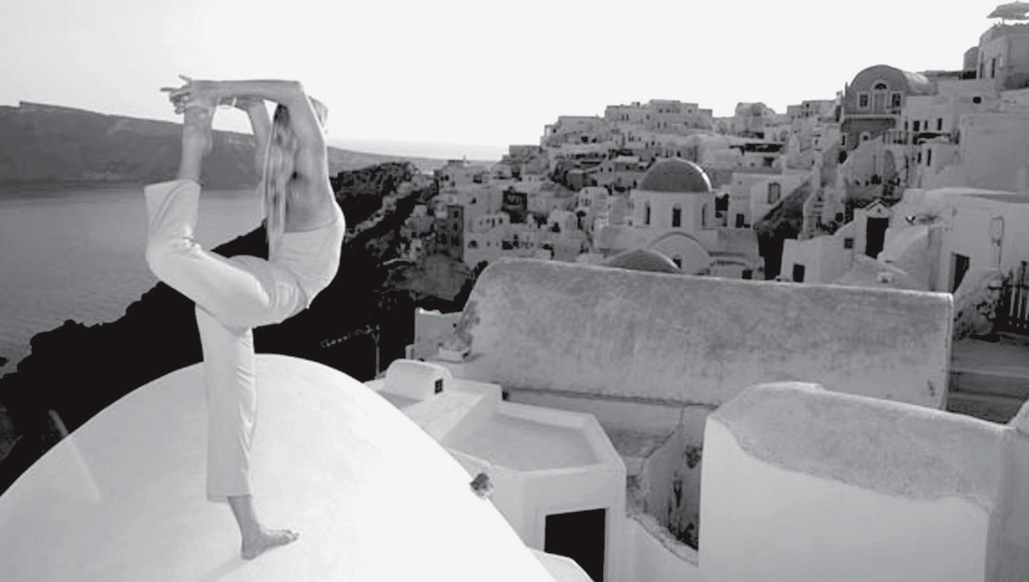 POSER—Shiva Rea, who will lead yoga classes at Bhakti Fest, salutes the sun above a Mediterranean town.