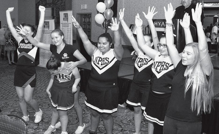FOR THE CAUSE— Above, the Conejo Sparkles Sparkles cheerleading squad does a routine for the guests. Members are, from left, Makayla Schmalz, Hannah Neiyer, Charlotte Bryman, Anna Rangel, Gia Vasquez, Diane Easley and Mckenna Kimball. At right, Westlake Village resident Rick Garboski tries to guess how many corks are in a vase, one of the many activities at the wine festival.
